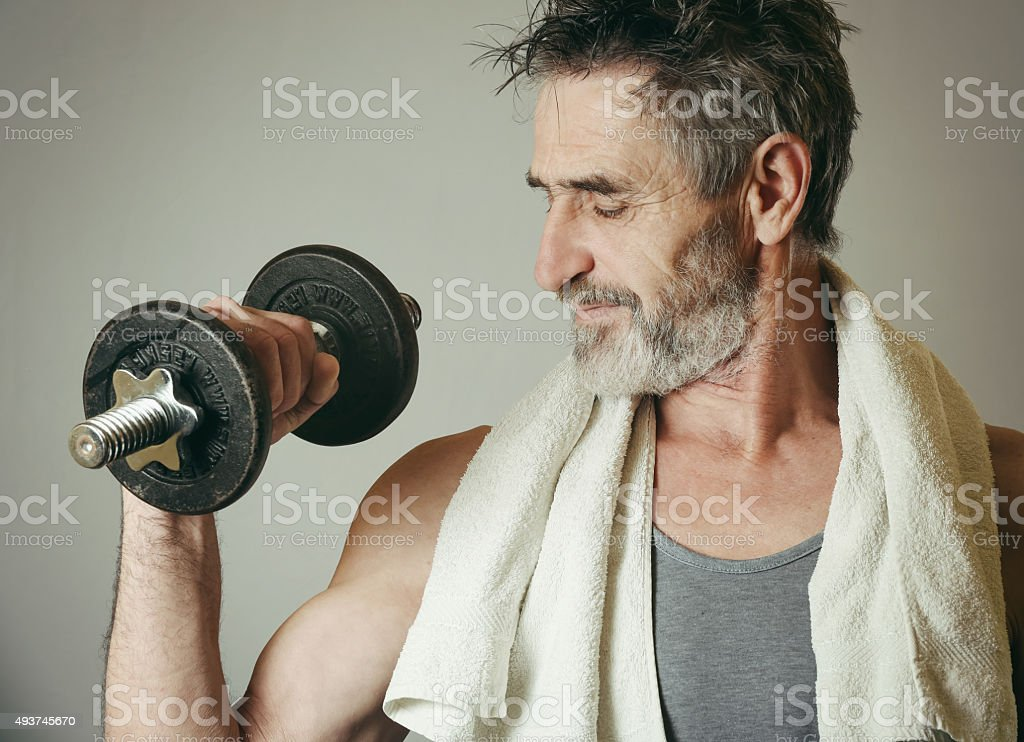 Senior man lifting weights stock photo