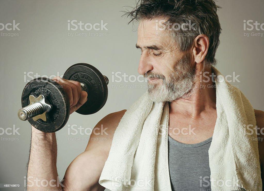 Senior man lifting weights stock photo