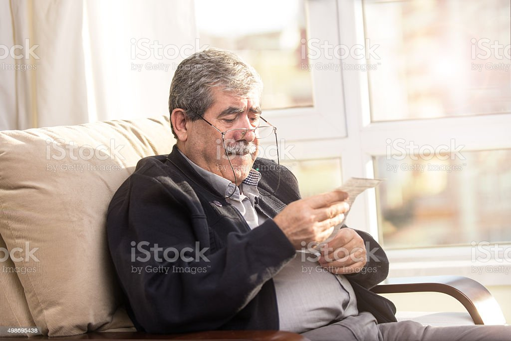 Senior man look bill with Shocked Expression stock photo