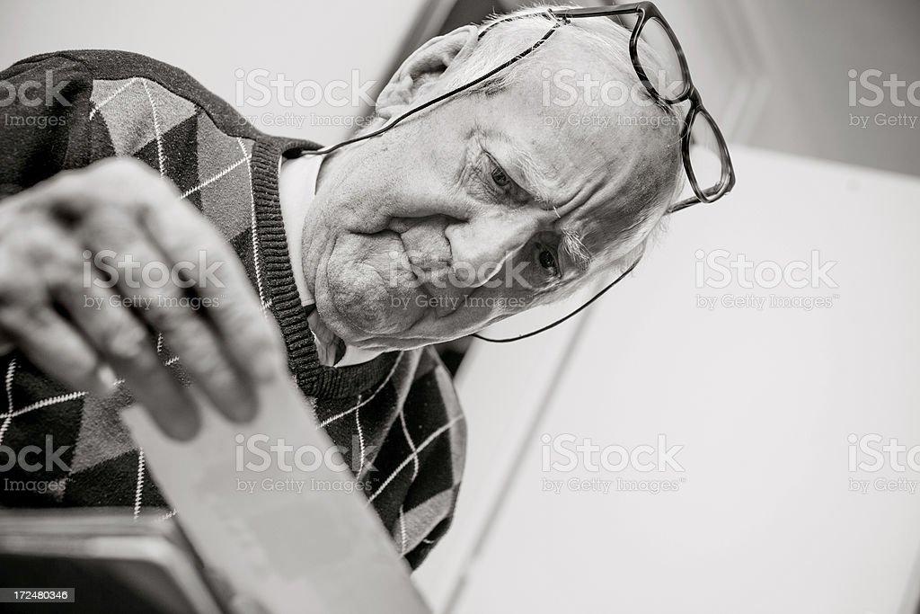 Senior man looking at an old photograph royalty-free stock photo