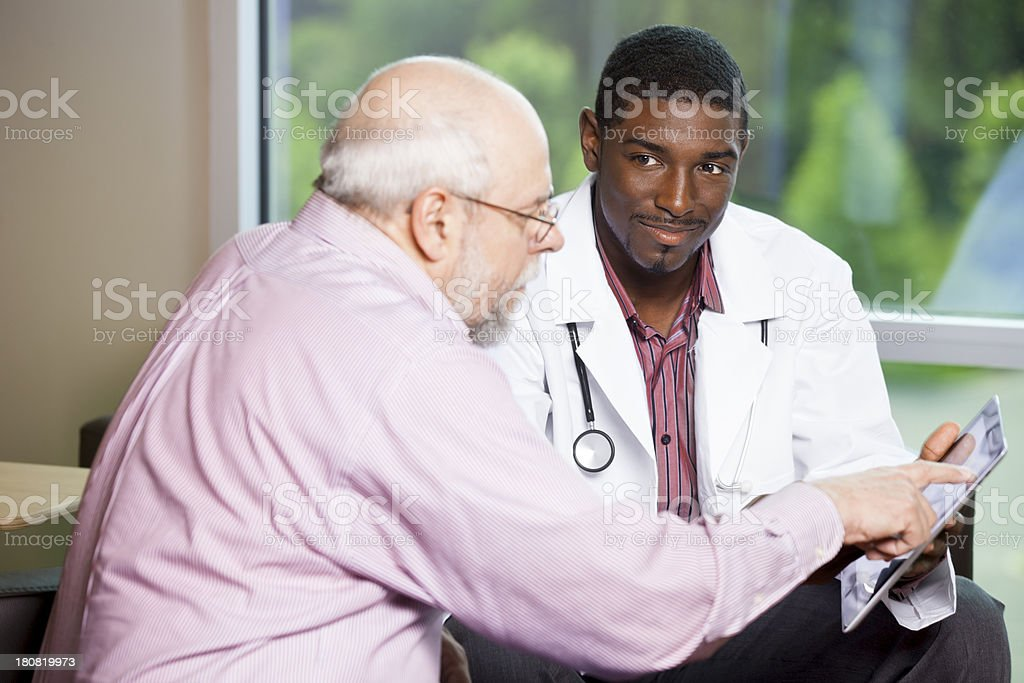 Senior man looking at information on digital tablet with doctor royalty-free stock photo