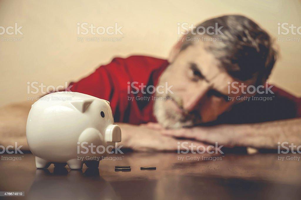 Senior man looking at piggy bank stock photo