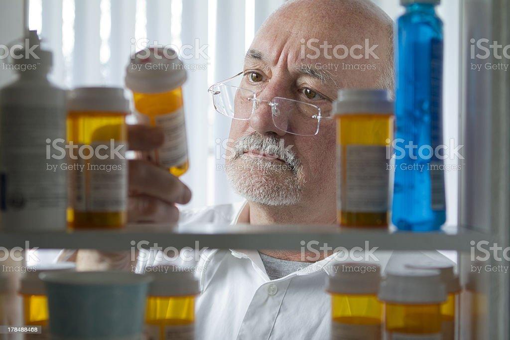 Senior man looking at prescription drugs stock photo