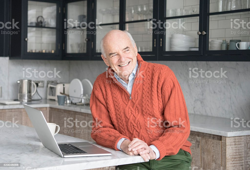 Senior man looking away in kitchen with laptop stock photo
