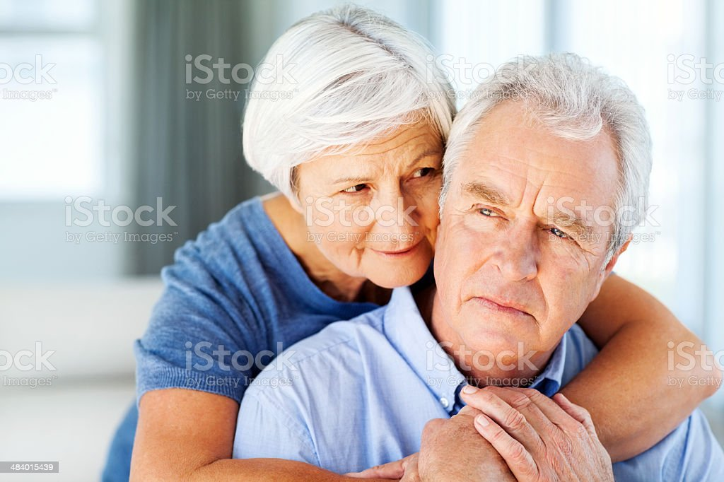 Senior Man Looking Away While Woman Embracing Him From Behind royalty-free stock photo