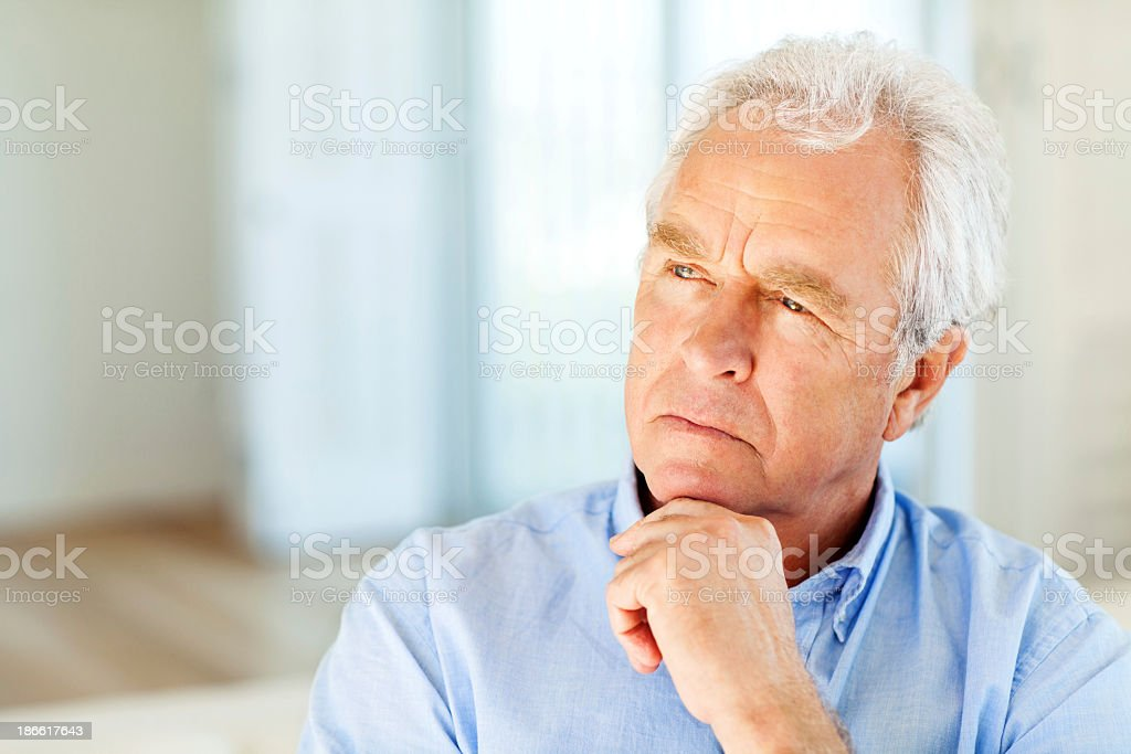 Senior Man Looking Away With Hand On Chin At Home royalty-free stock photo