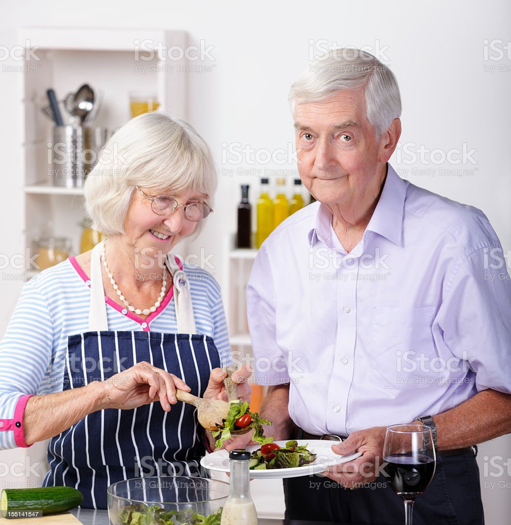 Senior Man Looking Concerned While Partner Dishes Salad stock photo