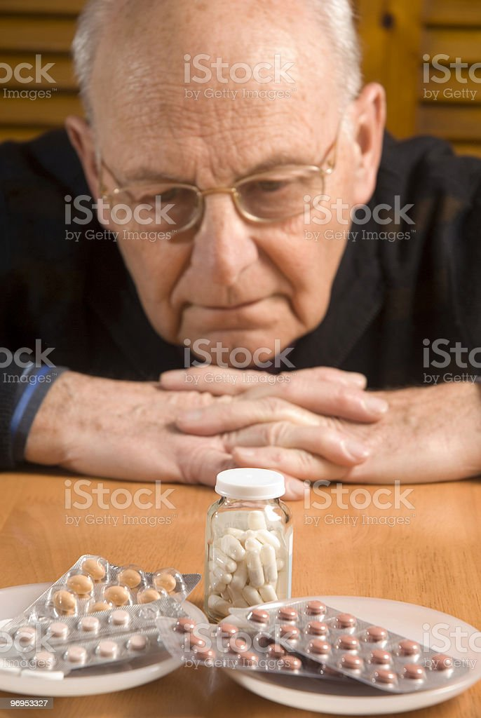 Senior man looks down at all of his different pills royalty-free stock photo