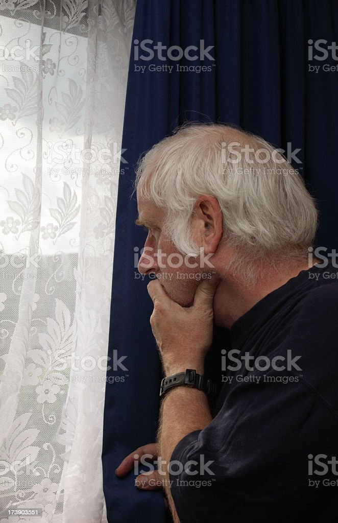 senior man looks out window - anxious nervous royalty-free stock photo