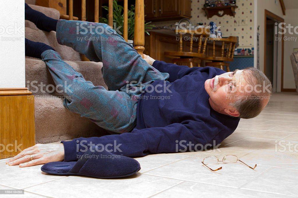 A senior man, lying disheveled, at the bottom of the stairs  stock photo