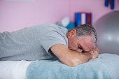 Senior man lying on a massage bed