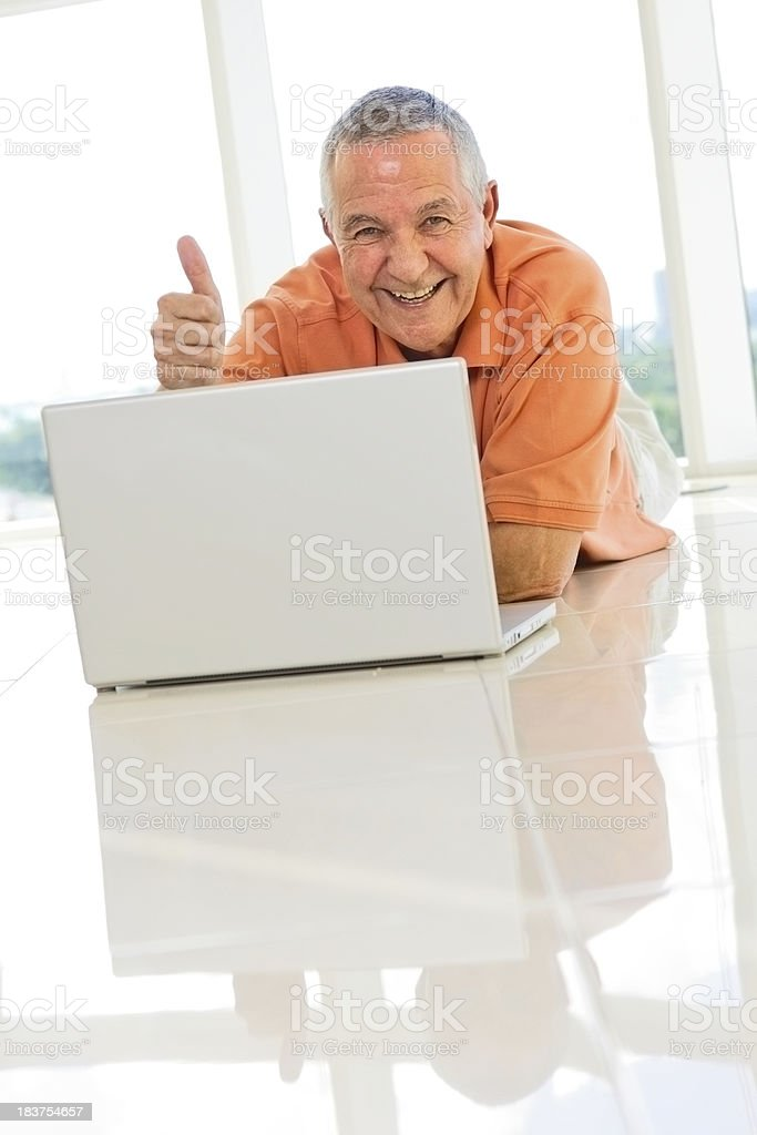Senior man lying on floor laptop and gesturing thumbs up royalty-free stock photo