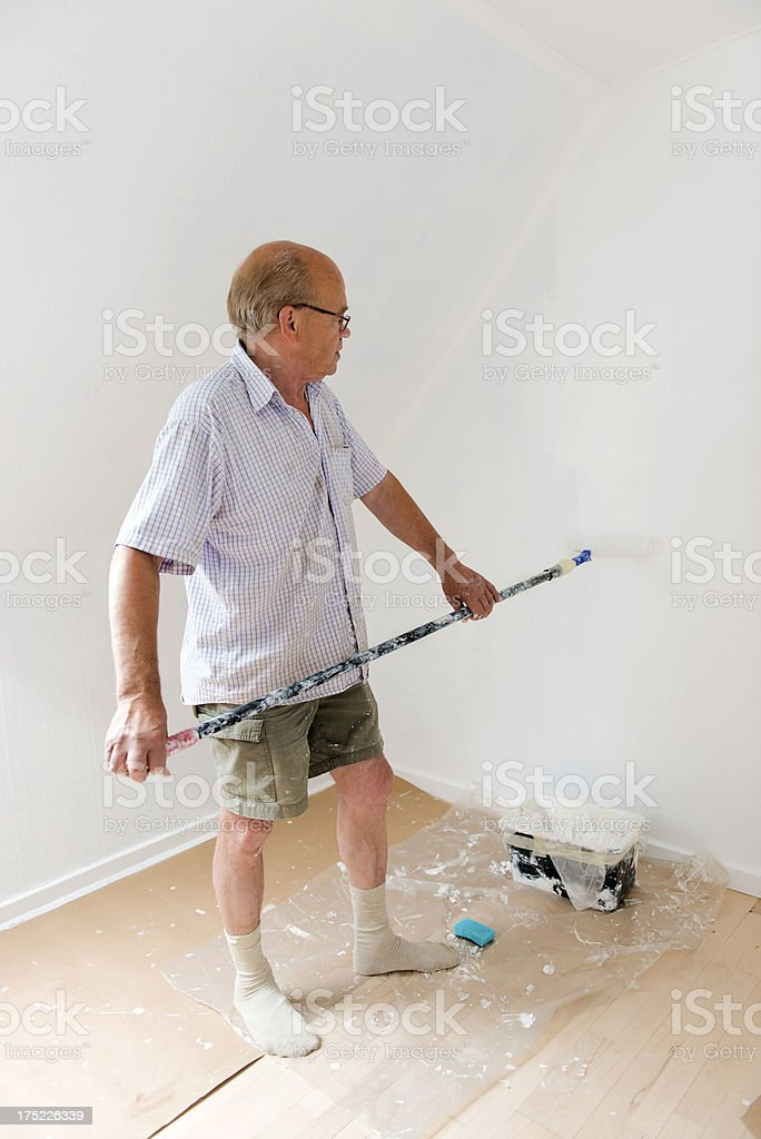 Senior man makes home improvement with new paint royalty-free stock photo