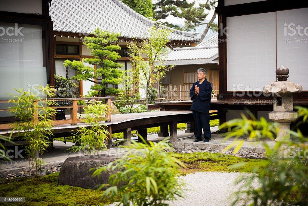 Senior man meditating at a temple stock photo