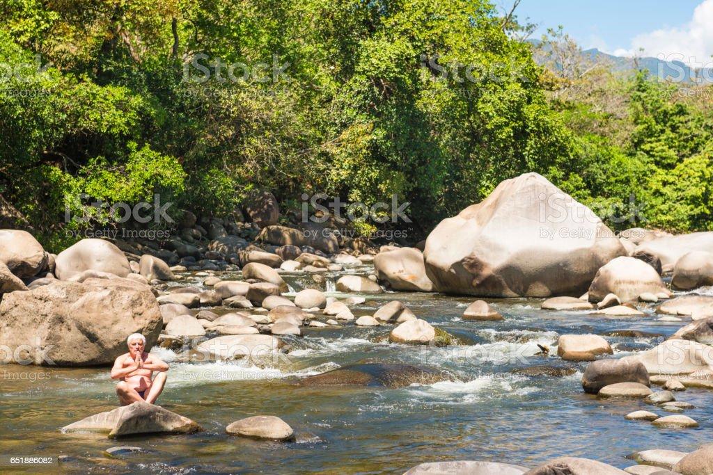 Senior man meditating in the river stock photo