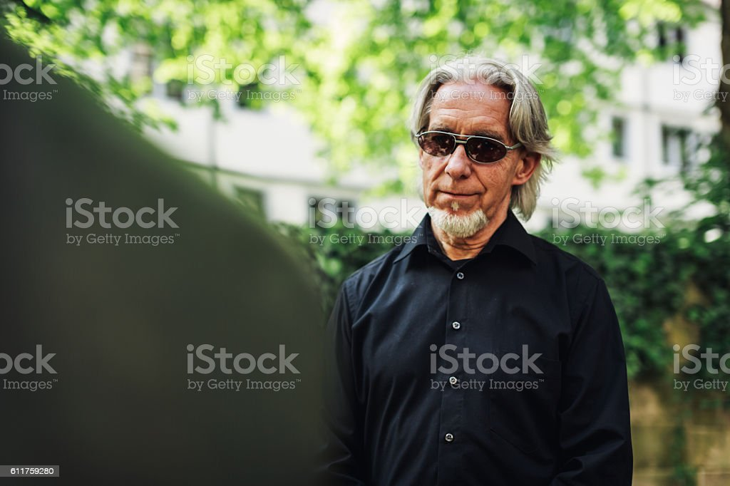 Senior man mourning by a beloved's grave stock photo