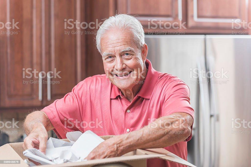 Senior man moving house, unpacking plates stock photo
