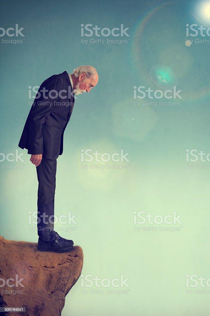 senior man on a cliff ledge stock photo