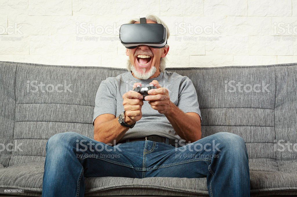 Senior man on couch, playing a VR game stock photo