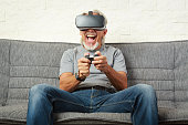 Senior man on couch, playing a VR game