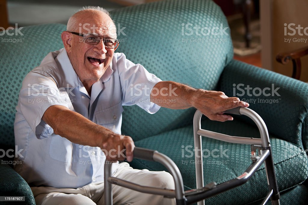 Senior man on couch with walker, laughing stock photo