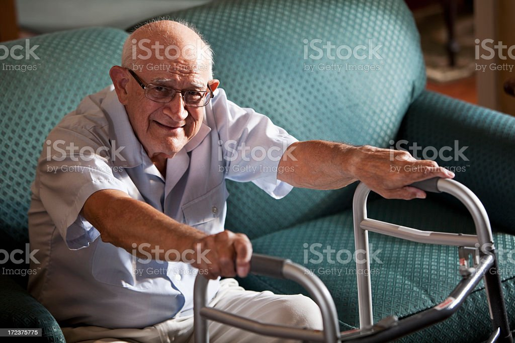 Senior man on couch with walker royalty-free stock photo