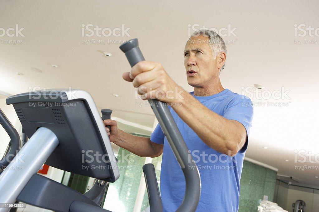 Senior Man On Cross Trainer In Gym stock photo