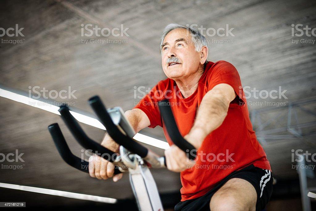 Senior Man on Spinning Bicycle stock photo