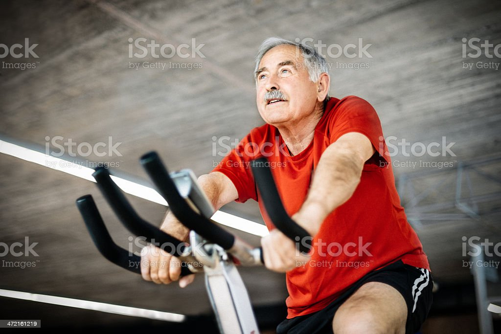 Senior Man on Spinning Bicycle stock photo