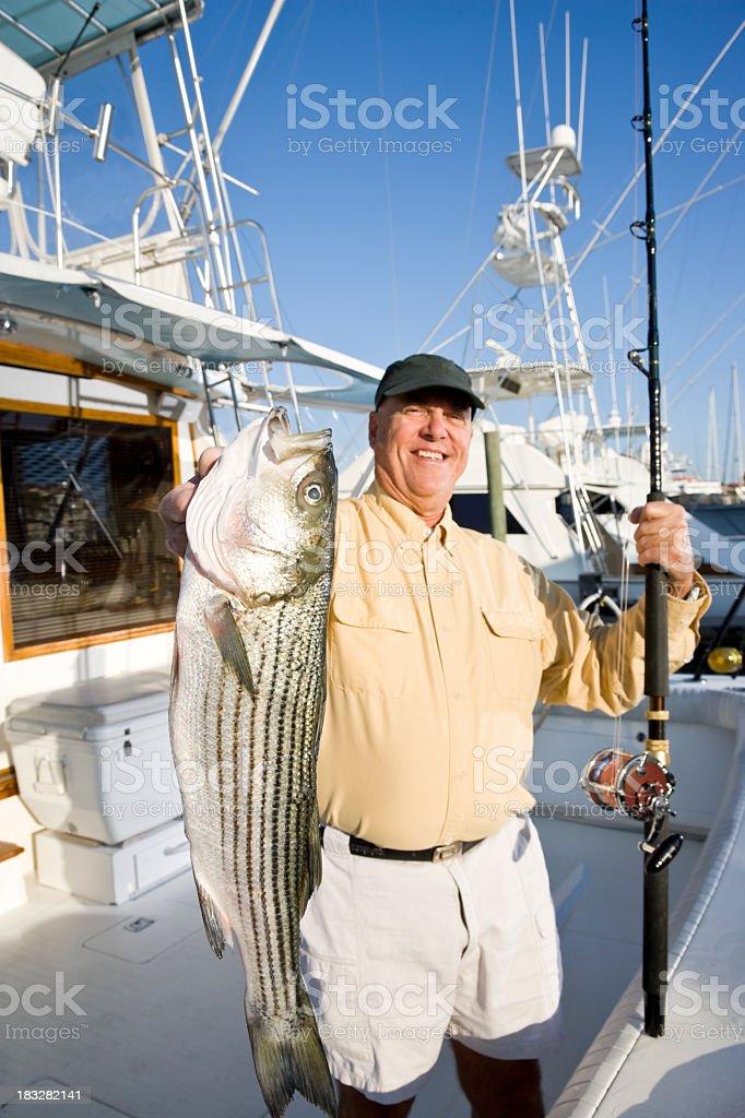 Senior man on fishing boat in marina with fresh catch stock photo