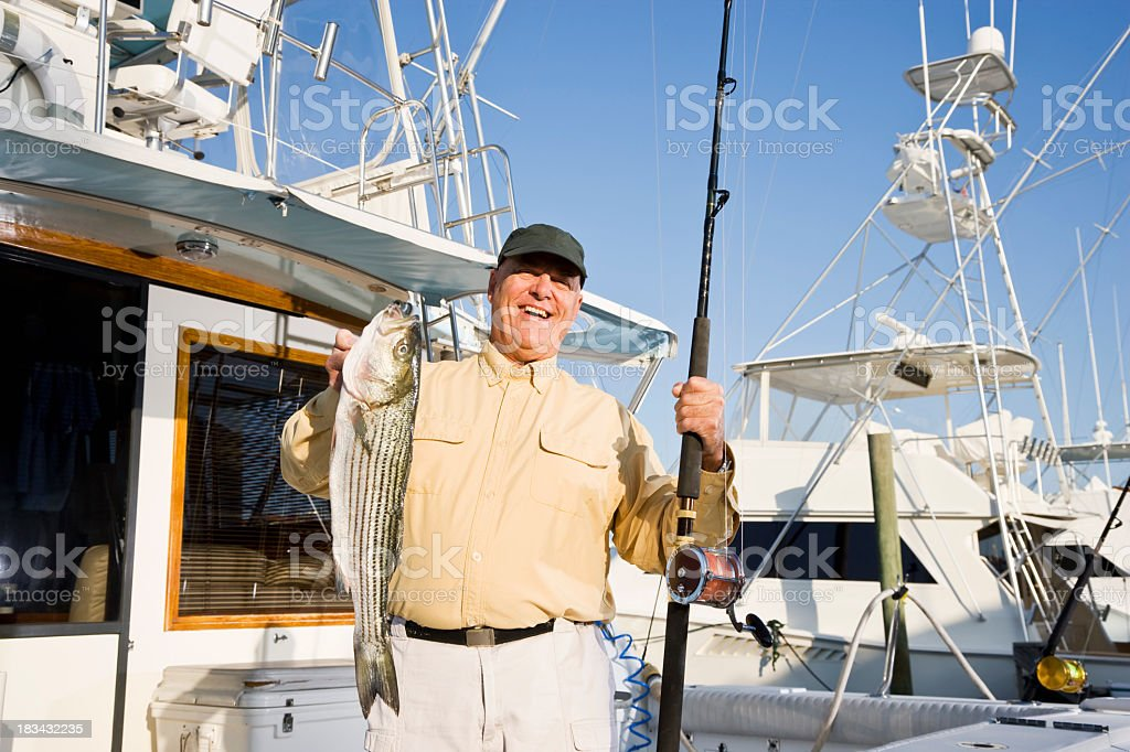 Senior man on fishing boat in marina with fresh catch stock photo