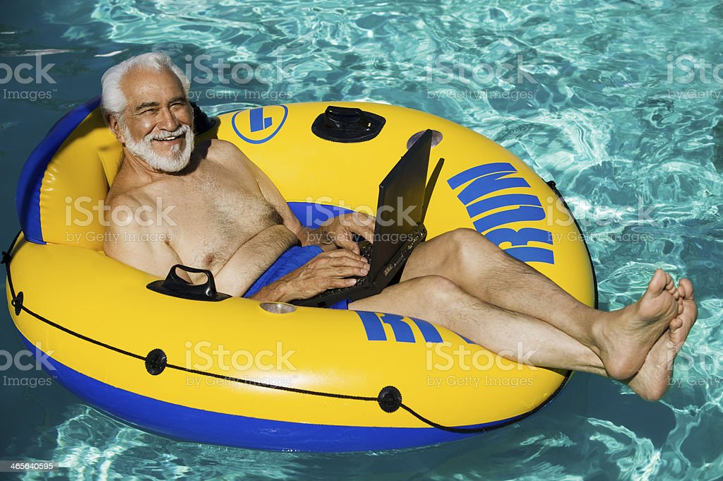 Senior Man on Float Tube Using Laptop stock photo
