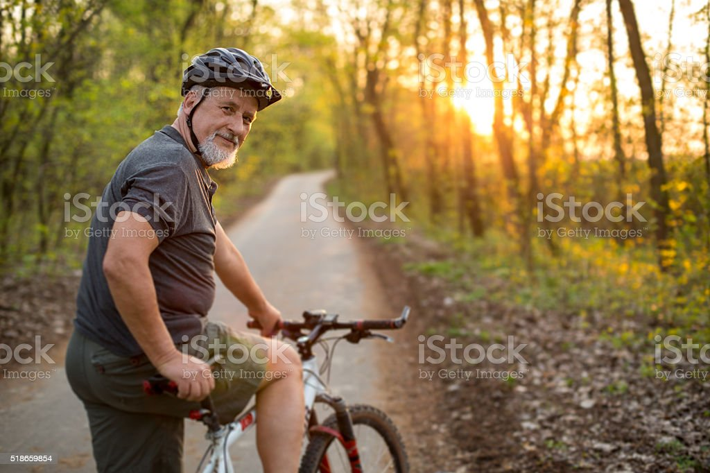 Senior man on his mountain bike outdoors stock photo