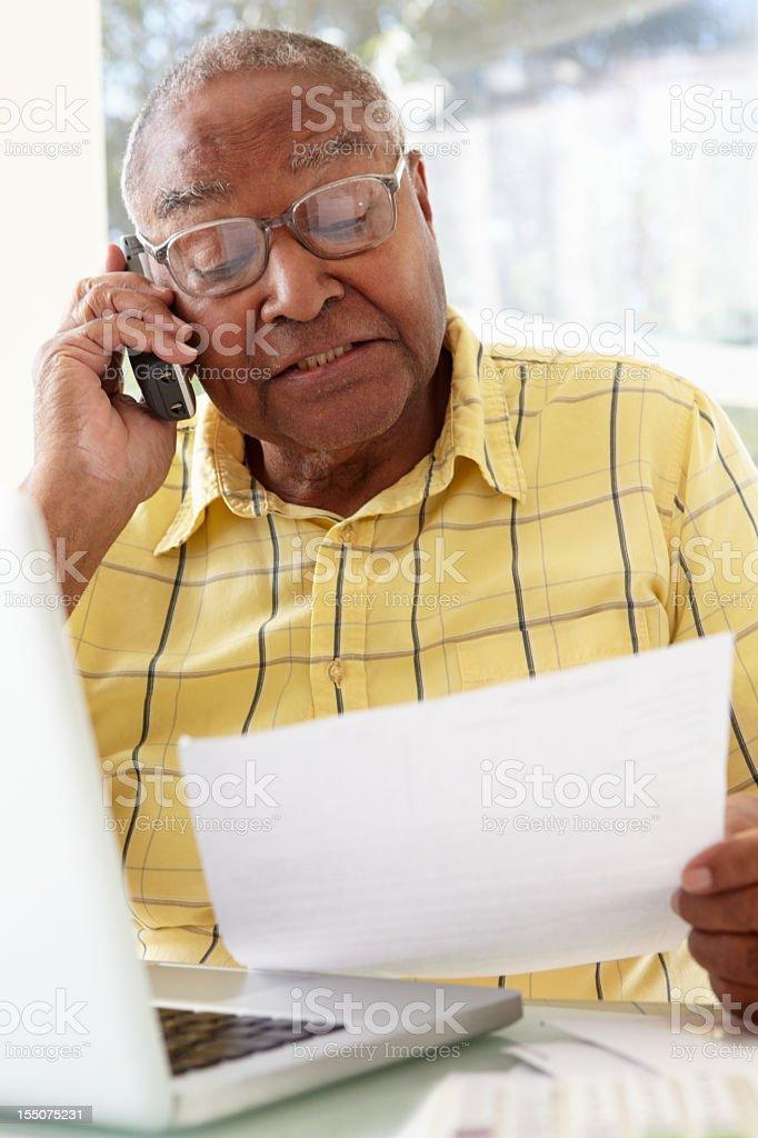 Senior Man On Phone Using Laptop At Home royalty-free stock photo