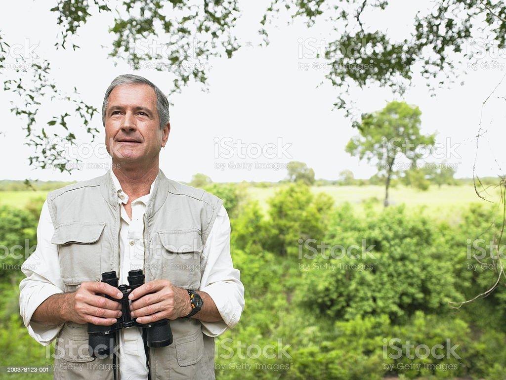 Senior man on safari holding binoculars, smiling royalty-free stock photo