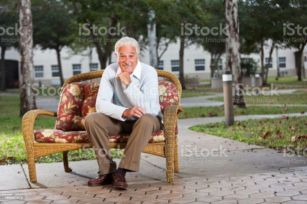 Senior man on sofa outdoors stock photo