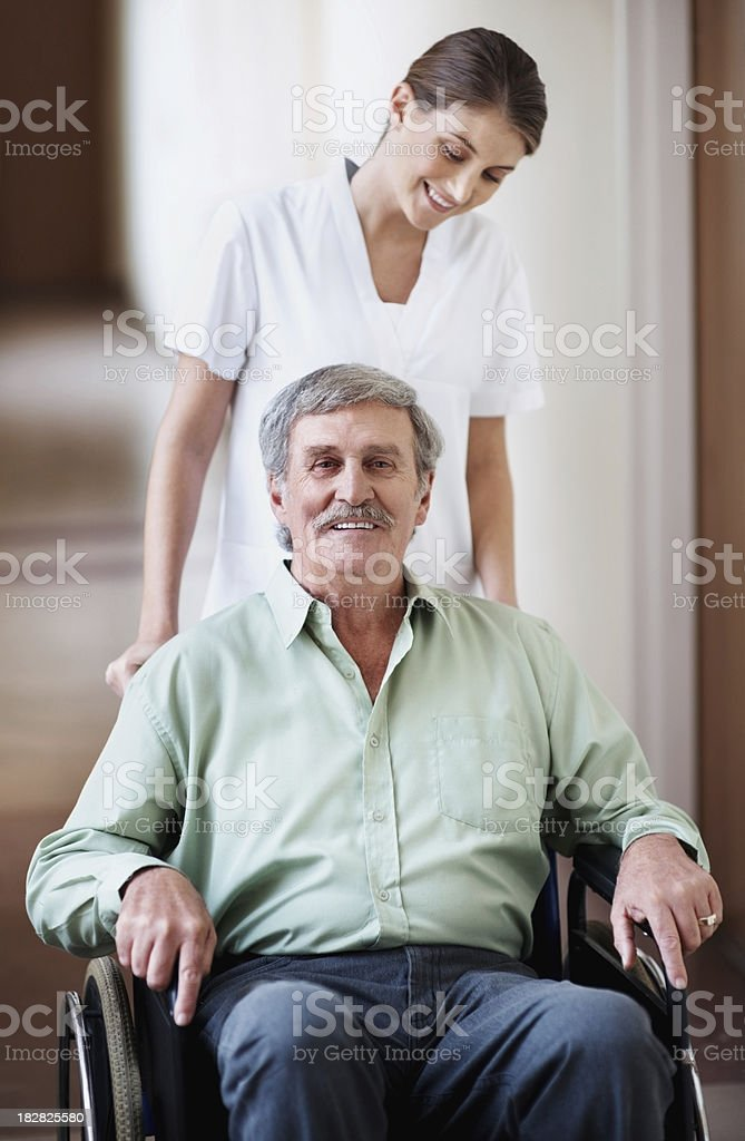 Senior man on wheelchair with a female nurse for assistance royalty-free stock photo