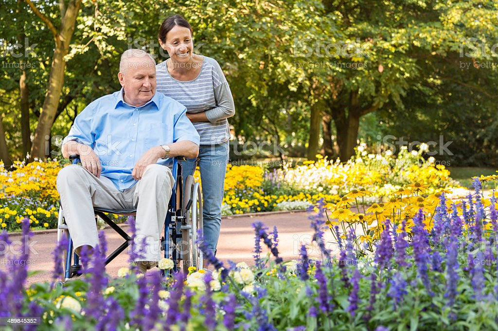 Senior man on wheelchair with home caregiver outdoors stock photo