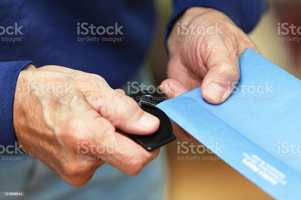 Senior Man Opening Envelope Using Letter Opener stock photo