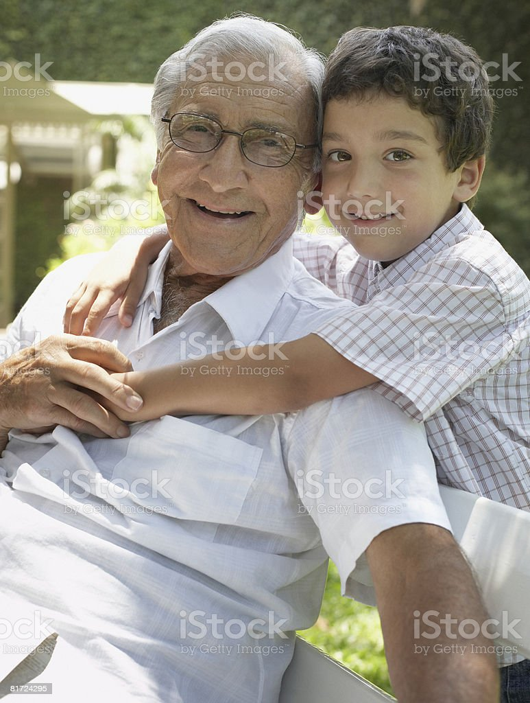 Senior man outdoors sitting on bench with young boy being affectionate toward him and smiling stock photo