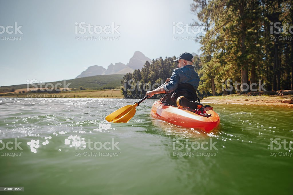 Senior man paddling kayak on a summer day stock photo