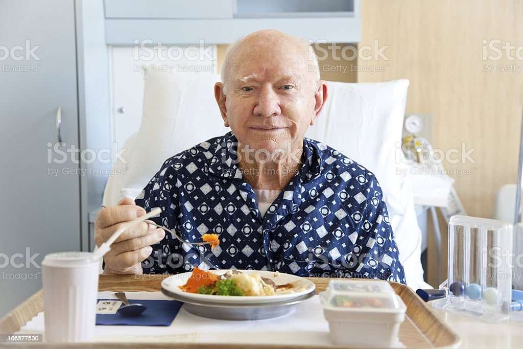 Senior man patient in hospital eating lunch stock photo