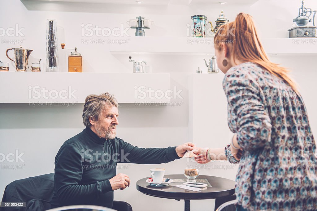 Senior Man Paying for Cappuccino to Female Barista, Caffe Trieste stock photo