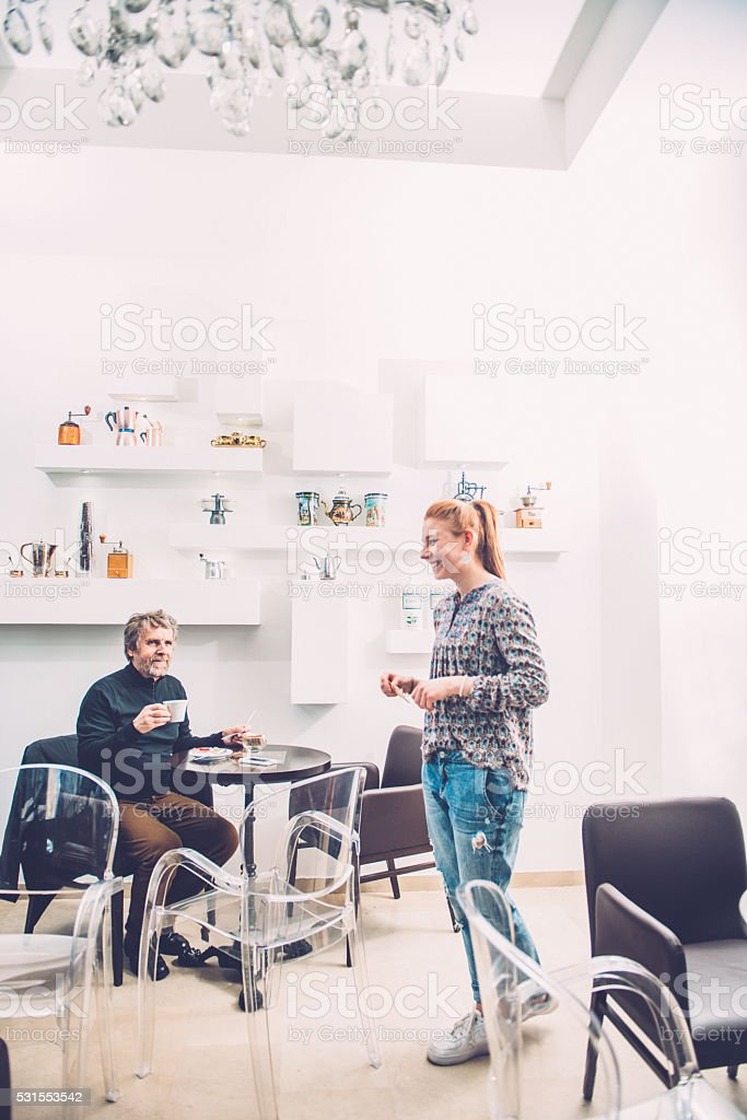 Senior Man Paying for Cappuccino to Pretty Barista, Caffe Trieste stock photo