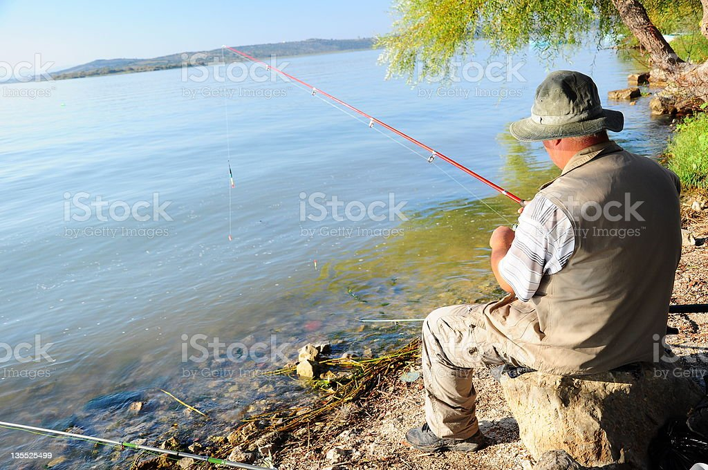 Senior man peacefully line-fishing on a lakeshore stock photo