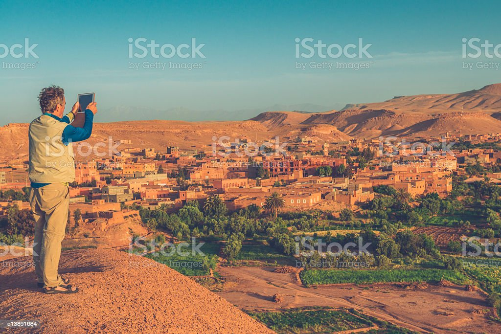 Senior Man Photographing Aït Benhaddou with Digital Tablet, Morocco, Africa stock photo