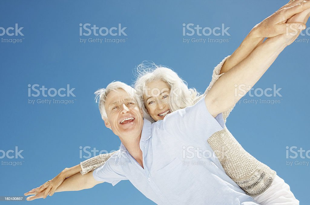 Senior man piggybacking his wife royalty-free stock photo