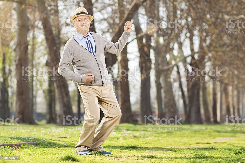 Senior man playing air guitar in the park stock photo