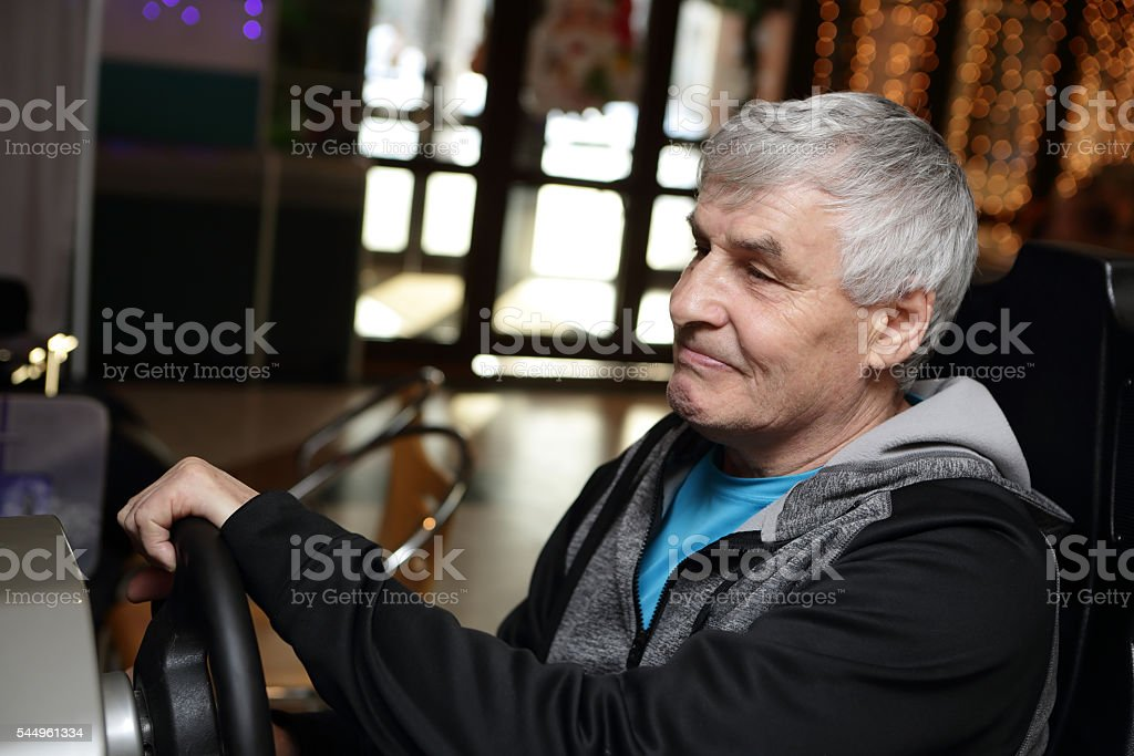 Senior man playing arcade game machine stock photo