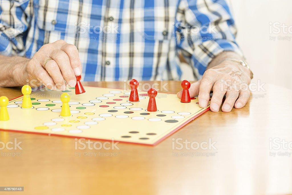 Senior man playing board game ludo royalty-free stock photo